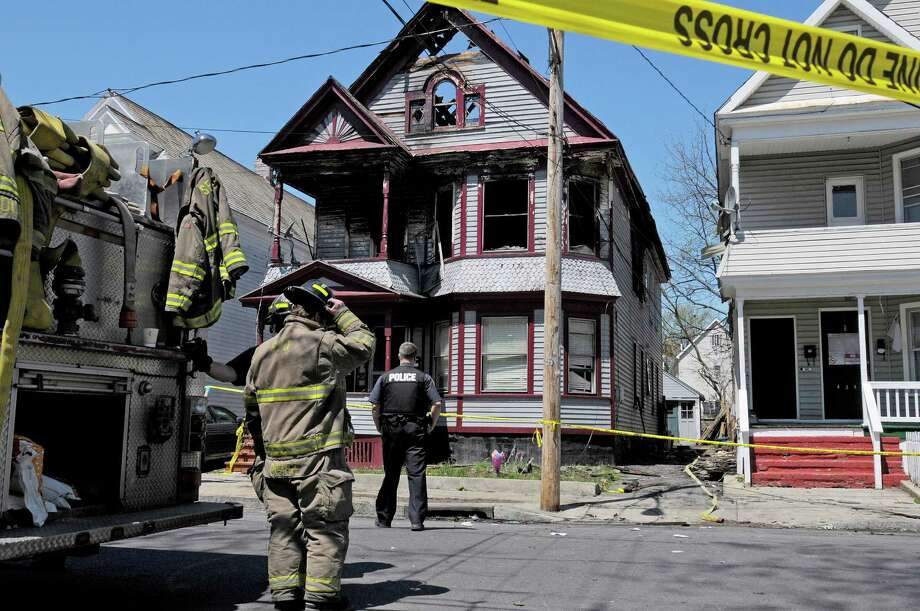 Firefighters and police at the scene of a house fire at 438 Hulett St. on Thursday, May 2, 2013 in Schenectady, NY.  Police said that four of the five people pulled from a burning home early Thursday morning  have died.  Three children and one adult died.   (Paul Buckowski / Times Union) Photo: Paul Buckowski