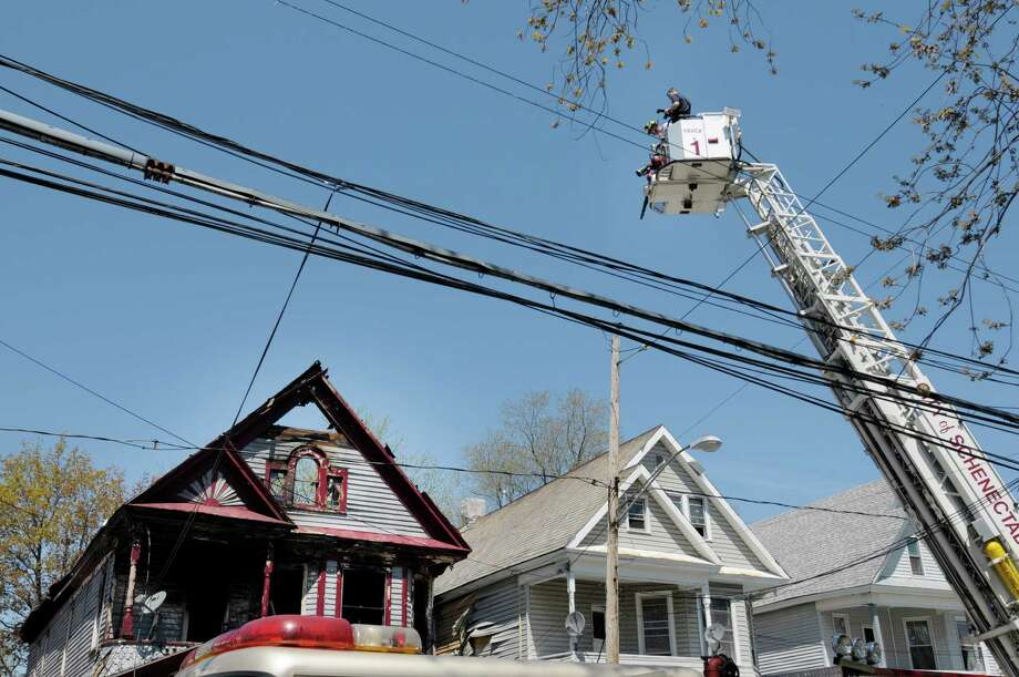 Fire investigators use a bucket truck to get a view at the scene of a house fire at 438 Hulett St. on Thursday, May 2, 2013 in Schenectady, NY.  Police said that four of the five people pulled from a burning home early Thursday morning  have died.  Three children and one adult died.   (Paul Buckowski / Times Union) Photo: Paul Buckowski