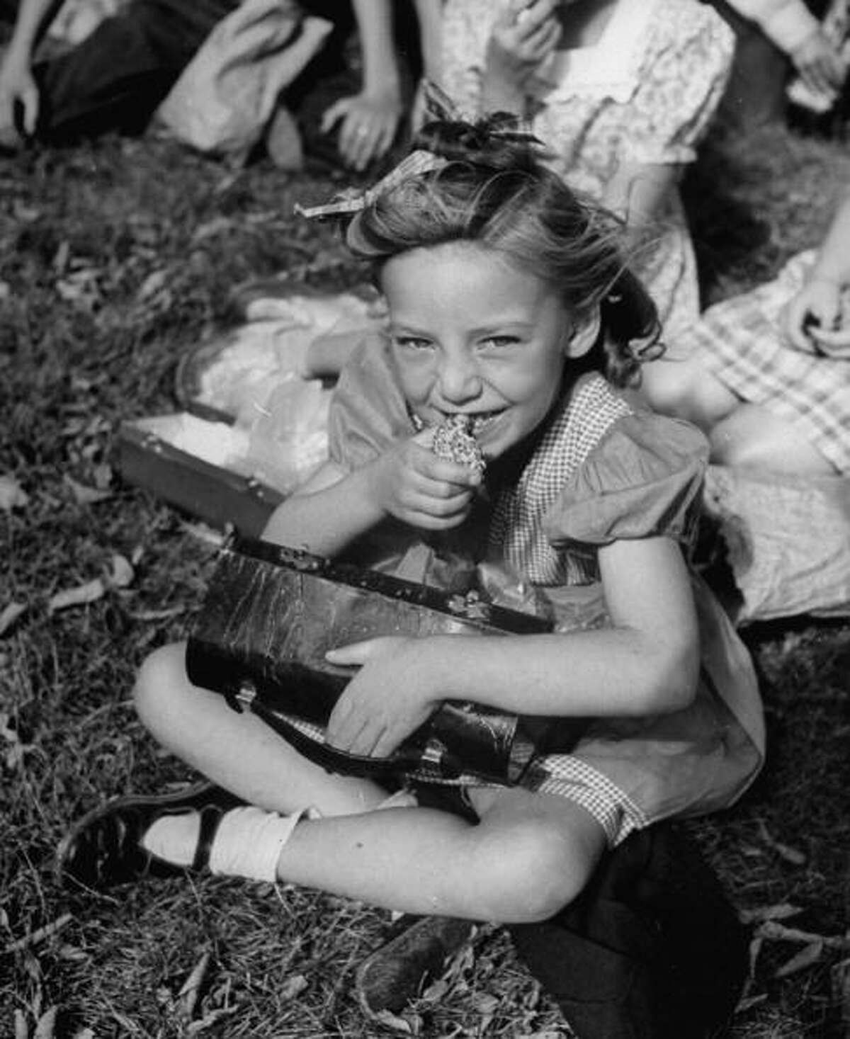 A little girl eating lunch outside at school in 1946. Keep clicking for photos of school lunches then, and now.