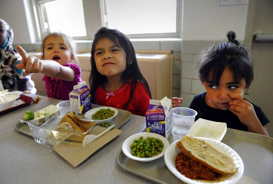 Fairview Elementary School ECE student, Amyi'ah Simpson, 4-years-old, right, eats her last remaining carrot, but is not sure about the spaghetti and peas at lunch time in the school cafeteria in 2011.