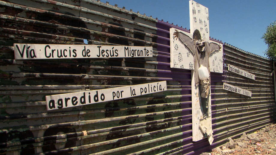 """A section of fence along the U.S.-Mexico border is decorated with religious and political images and signs related to immigration issues, in """"Harvest of Empire."""" Photo: Jimmy Felter, Handout / ONLINE_YES"""