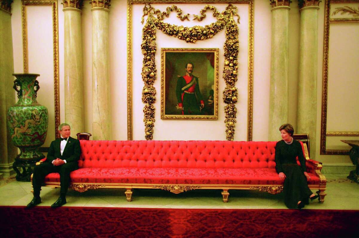 President George W. Bush and Mrs. Laura Bush sit on either ends of a couch prior to a social event at Buckingham Palace. Photo by Eric Draper, Courtesy of the George W. Bush Presidential Library and Museum