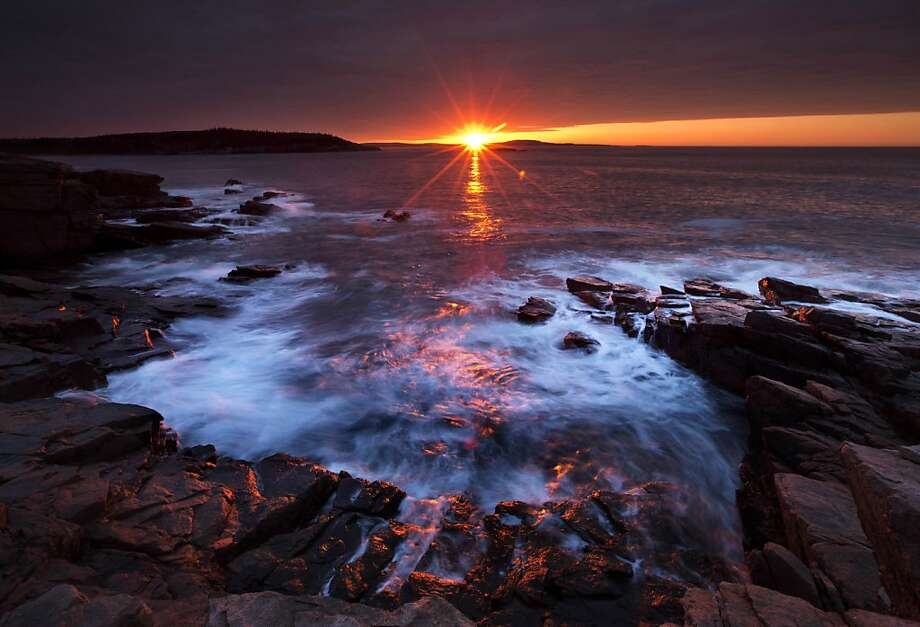 The rising sun's rays bathe the rocky coast of Acadia National Park, Maine. Photo: Robert F. Bukaty, Associated Press