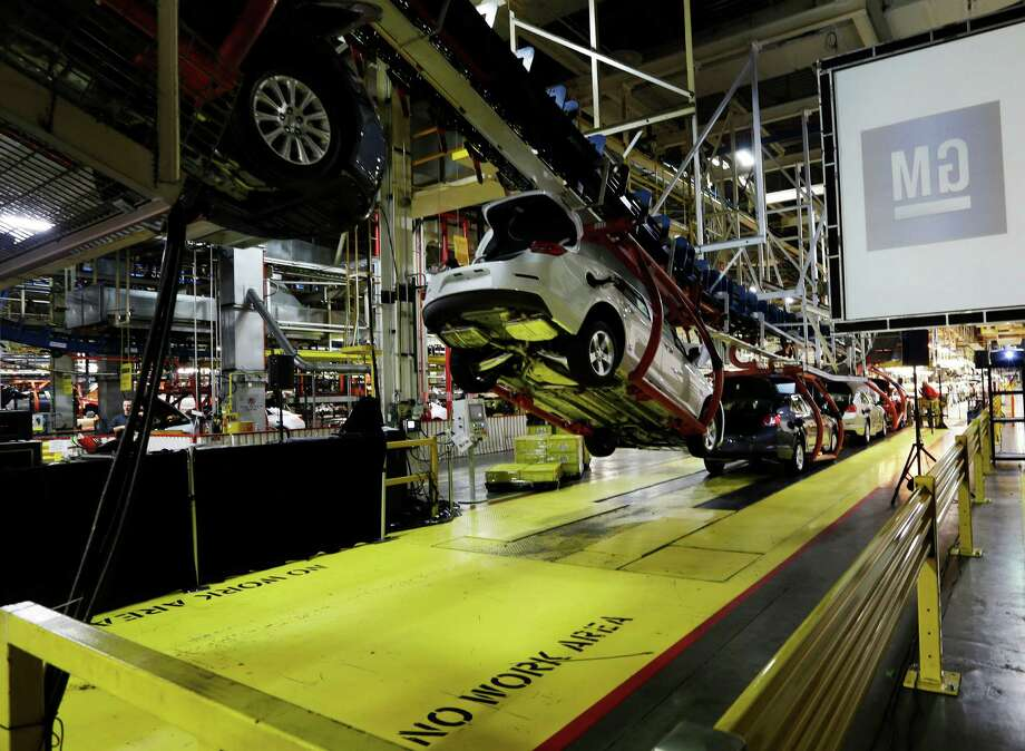 In this Monday, Jan. 28, 2013 file photo, cars move along an assembly line at the General Motors Fairfax plant in Kansas City, Kan. General Motors' net income fell 14 percent in the first quarter, as it earned less money in North America while preparing to launch a redesigned version of its best-selling vehicle, the Silverado pickup. (AP Photo/Orlin Wagner, File) Photo: Orlin Wagner