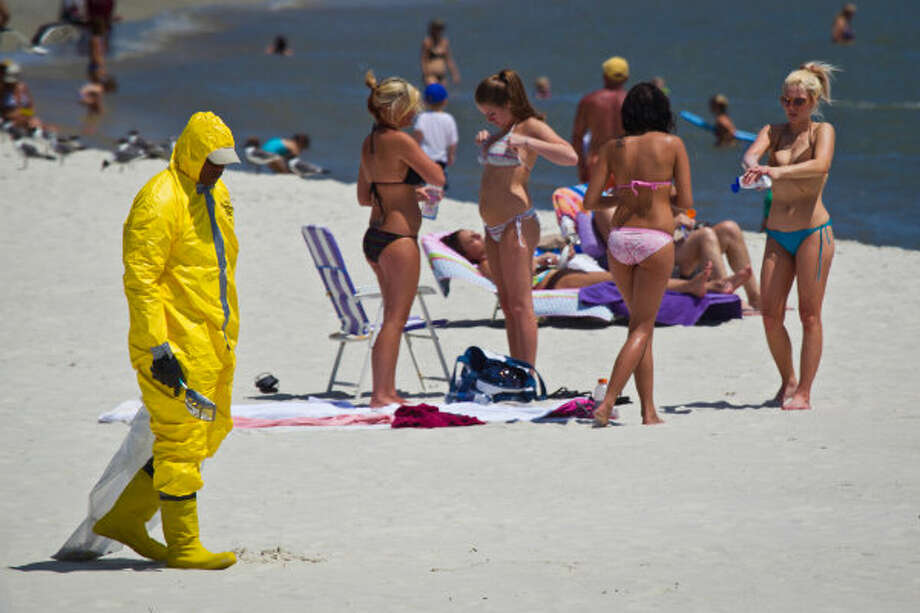 A cleanup worker, wearing a protective coverall and carrying a small scoop, punctuates an otherwise typical holiday beach scene as patrols the beach looking for tar balls on Independence Day 2010.Tourist business along the Gulf Coast all reported feeling the sting of lost income from a noticeable dip in tourism the summer following the Deepwater Horizon spill.