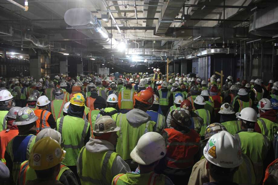 "Construction workers gather in a parking garage at the new ExxonMobil Houston campus for a weekly ""all hands"" meeting to discuss site safety."