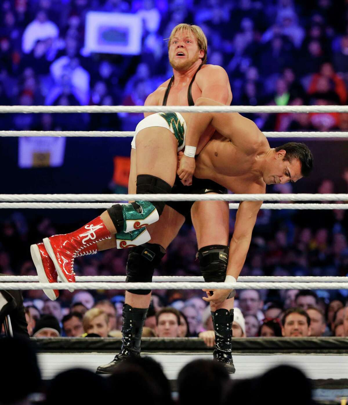"""Jacob """"Jake"""" Hager, Jr., known as Jack Swagger, top, lifts Jose Alberto Rodríguez, of Mexico, known as Alberto Del Rio as they wrestle Sunday, April 7, 2013, in East Rutherford, N.J., during the WWE Wrestlemania 29 event. (AP Photo/Mel Evans)"""