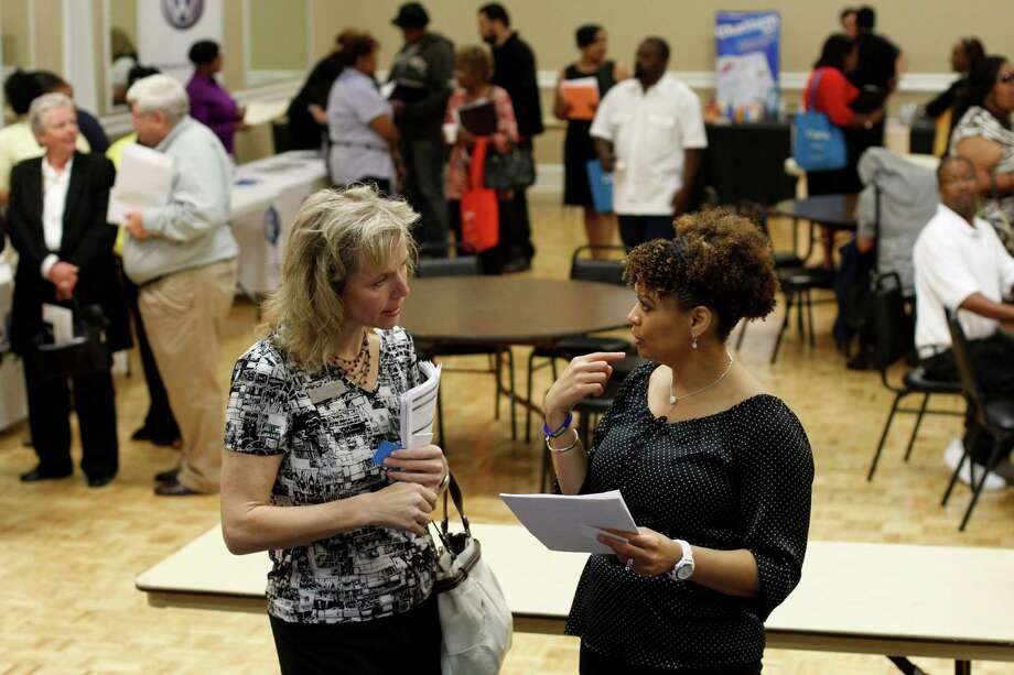 In this Tuesday, April 30, 2013, photo, Donna Van Natten, with The Enterprise Center, left, and Valoria Armstrong with the Tennessee American Water Co. converse during a job fair being held at the Urban League in Chattanooga, Tenn. The Labor Department reports on the number of Americans who applied for unemployment benefits last week on Thursday, May 2, 2013. (AP Photo/Chattanooga Times Free Press, Dan Henry) Photo: Dan Henry