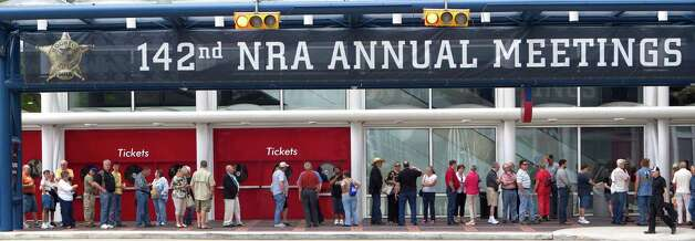 Attendees line up outside the George R. Brown Convention Center before the opening of the National Rifle Association's 142 Annual Meetings and Exhibits at the George R. Brown Convention Center Thursday, May 2, 2013, in Houston. 