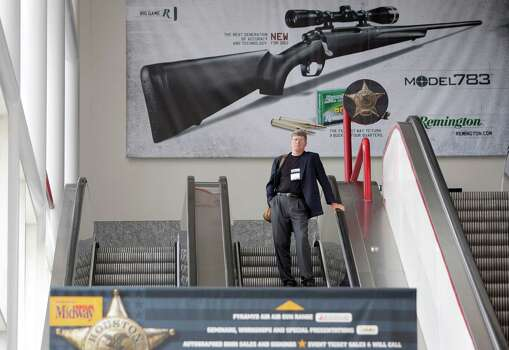 An NRA attendee makes his way down an escalator as exhibitors began setting up in preparation for the National Rifle Association's 142 Annual Meetings and Exhibits at the George R. Brown Convention Center Thursday, May 2, 2013, in Houston. 