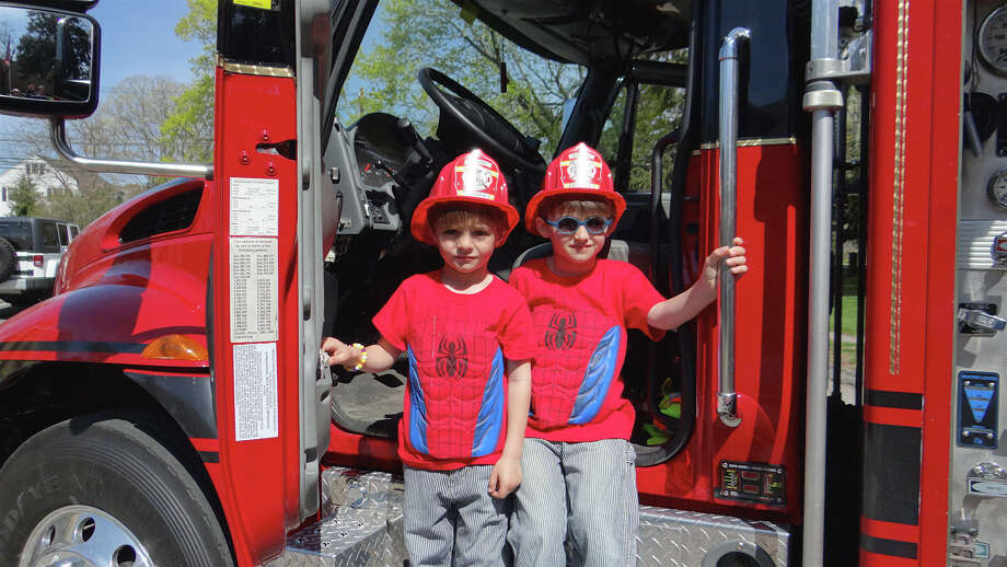 Fairfield twins Arthur and Augustine Zarra, 5, check out Southport Fire Department's Squad 14 truck Saturday at the YMCA's Healthy Kids Day. Photo: Mike Lauterborn / Fairfield Citizen contributed