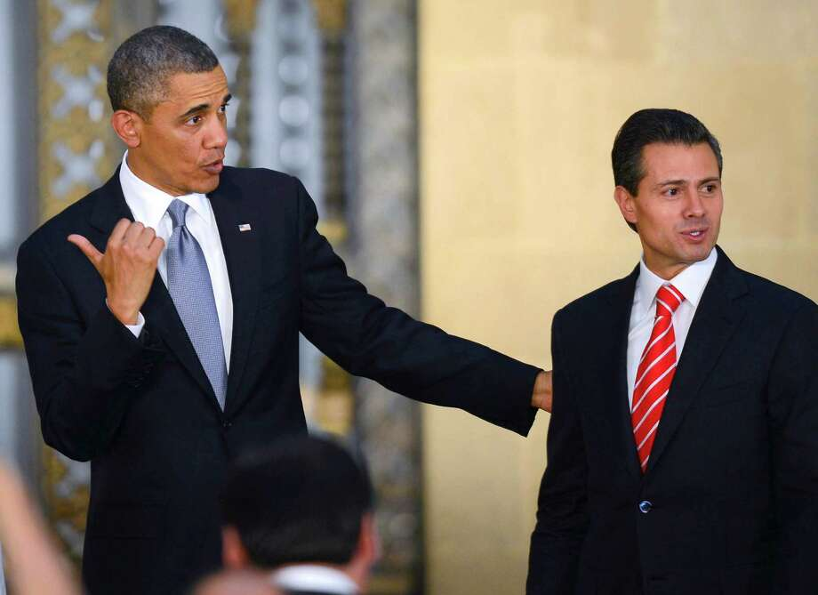 US President Barack Obama (L) gestures next to Mexican President Enrique Pena Nieto after offering a joint press conference at the National Palace in Mexico City on May 2, 2013. Obama landed in Mexico on Thursday at the start of a three-day trip that will also take him to Costa Rica, with trade, US immigration reform and the drug war high on the agenda.  AFP PHOTO/Alfredo ESTRELLAALFREDO ESTRELLA/AFP/Getty Images Photo: ALFREDO ESTRELLA, AFP/Getty Images / AFP