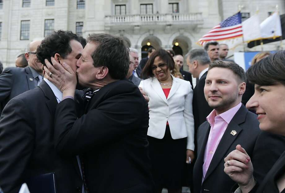 Rhode Island House Speaker Gordon Fox, left, is kissed by R.I. Rep. Frank Ferri, D-Warwick, after a gay marriage bill was signed into law outside the State House in Providence, R.I., Thursday, May 2, 2013.  Photo: Charles Krupa, Associated Press