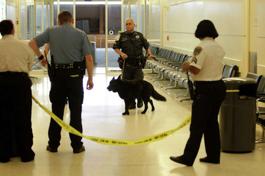 Police work in the passenger pickup exit area after a shooting near a ticket counter in the pre-screening area of Terminal B at Bush Intercontinental Airport Thursday, May 2, 2013, in Houston. ( Melissa Phillip / Houston Chronicle Photo: CHRON, Staff / © 2013  Houston Chronicle