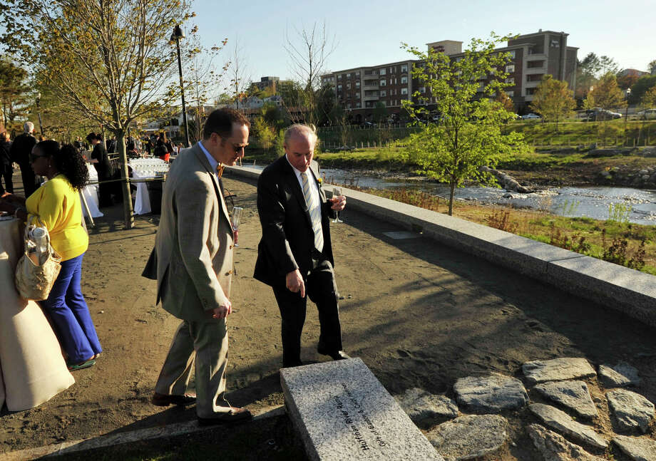 Arthur Selkowitz, right, shows his son, Jed, an inscription in a rock at the reception following the ribbon cutting ceremony at the newly opened Mill River Park in Stamford on Thursday, May 2, 2013. Arthur is the chairman of the Mill River Collaborative. Photo: Jason Rearick / Stamford Advocate