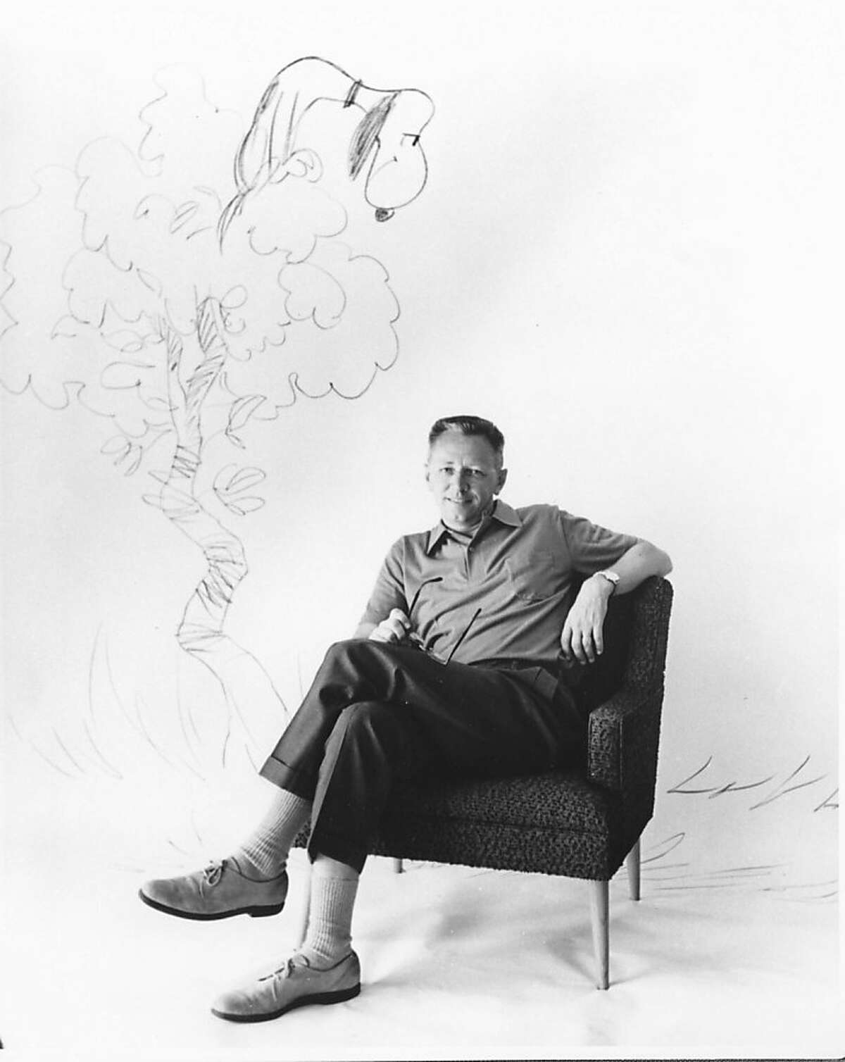 Charles Schulz sitting in a mid-century modern chair and Snoopy in the background as a vulture