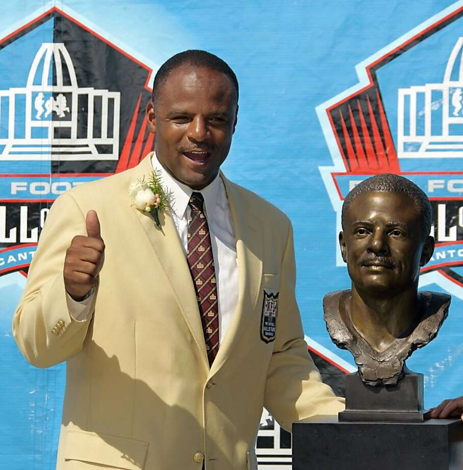 Former NFL great Warren Moon poses with his bust after enshrinement into the Pro Football Hall of Fame Saturday, Aug. 5, 2006, in Canton, Ohio. Moon quarterbacked the CFL Edmonton Eskimos before his NFL career with the Houston Oilers, Seattle Seahawks and Kansas City Chiefs. (AP Photo/Mark Duncan)