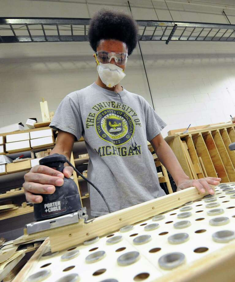 Luis Whitehead, 22, of Schenectady uses a sander to smooth a piece of wood while working at Halfmoon Works on Thursday, May 2, 2013 in Halfmoon, N.Y.   (Lori Van Buren / Times Union) Photo: Lori Van Buren / 10022225A