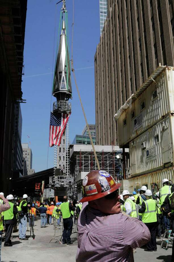 A worker holds a guide rope as the final piece of spire is hoisted to the roof of One World Trade Center, Thursday, May 2, 2013 in New York.  The piece will be attached to the spire at a later date, capping off the tower at 1,776 feet. (AP Photo/Mark Lennihan) Photo: Mark Lennihan, STF / AP
