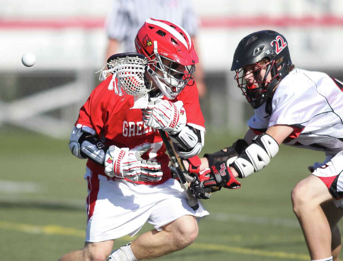Greenwich attackman Jamie Paradise has the ball poked away by New Canaan defender Graham Wagner during FCIAC action in New Canaan. New Canaan tripped up the Cards, 12-0. © J. Gregory Raymond for The Greenwich Time