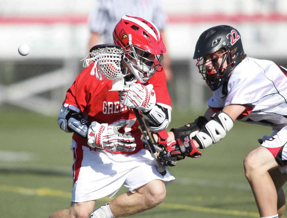Greenwich attackman Jamie Paradise has the ball poked away by New Canaan defender Graham Wagner during FCIAC action in New Canaan. New Canaan tripped up the Cards, 12-0. © J. Gregory Raymond for The Greenwich Time Photo: J. Gregory Raymond / Stamford Advocate Freelance;  © J. Gregory Raymond