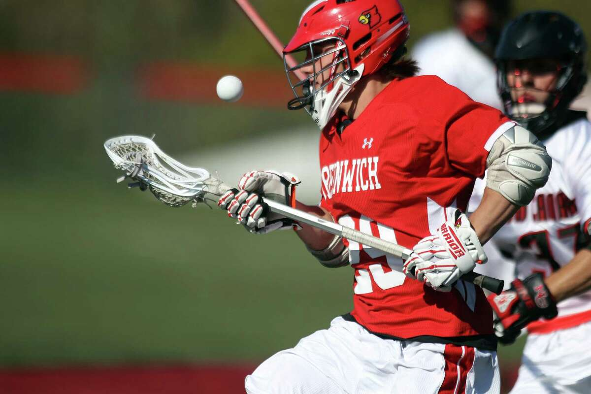 Greenwich High's Graham Savio chases a loose ball as New Canaan's Eric Persky pursues on Thurday, May 2, 2013 in New Canaan.