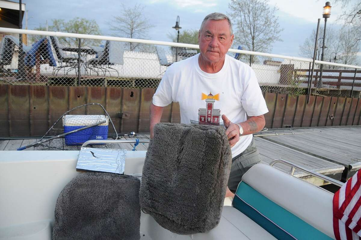 George Kosa displays two gasoline-soaked cushions he found floating in the Hudson River shortly after a plane crash. (Lance Wheeler / Special to the Times Union)