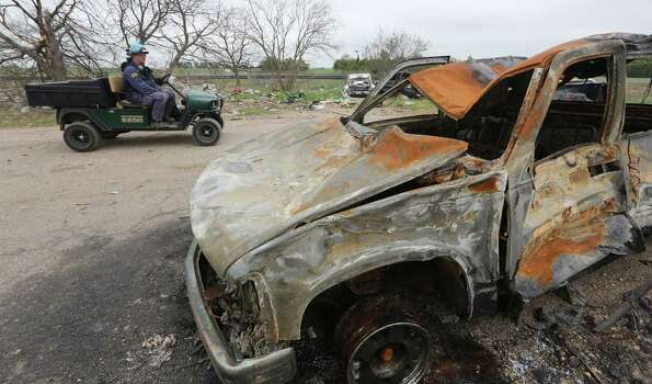 Investigator drive past a burned truck during their investigation of the destroyed fertilizer plant in West, Texas, Thursday, May 2, 2013. Investigators face a slew of challenges in figuring out what caused the explosion at the fertilizer plant that killed 14 people and destroyed part of the small Texas town. (AP Photo/Pool/ LM Otero) Photo: LM Otero, POOL / AP