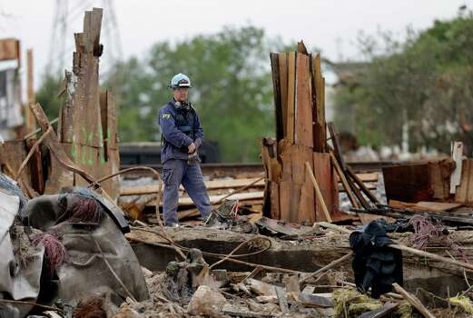 An investigator looks over a destroyed fertilizer plant in West, Texas, Thursday, May 2, 2013. Investigators face a slew of challenges in figuring out what caused the explosion at the fertilizer plant that killed 14 people and destroyed part of the small Texas town. (AP Photo/LM Otero, Pool) Photo: LM Otero, POOL / AP POOL