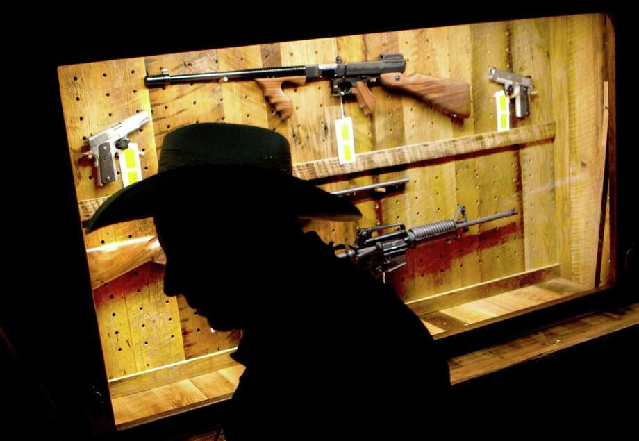 "Houstonian Sam Bennett walks past a ""Wall of Guns"" being raffled off by the NRA at the George R. Brown Convention Center. Photo: Johnny Hanson, Staff / © 2013  Houston Chronicle"