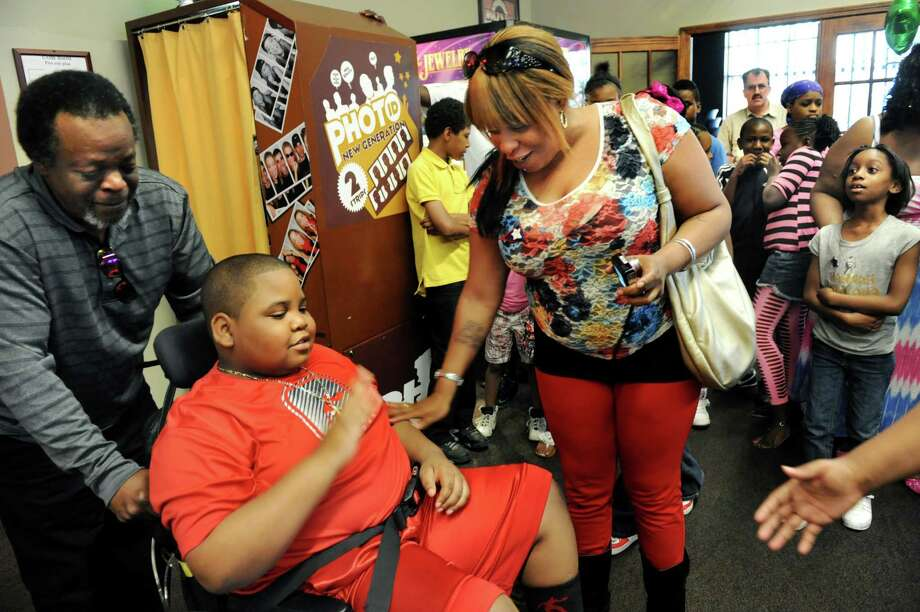 NaSeaph Williams, 10, of Saratoga Springs, center left, enters his surprise party and greets his biological mother, Sharona Howard of Troy, center, on Thursday, May 2, 2013, at Wolf's 111 in Colonie, N.Y. NaSeaph, who is terminally ill, celebrated his 11th birthday in advance of the actual date. At left is the man he calls father, Ronald Nelson. (Cindy Schultz / Times Union) Photo: Cindy Schultz / 10022256A
