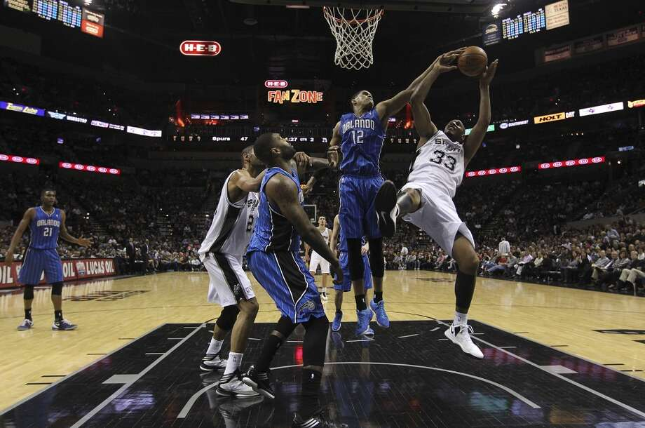 The Spurs' Boris Diaw is fouled by Orlando Magic's Tobias Harris at the AT&T Center on April 3, 3013. The Spurs won 98-84.
