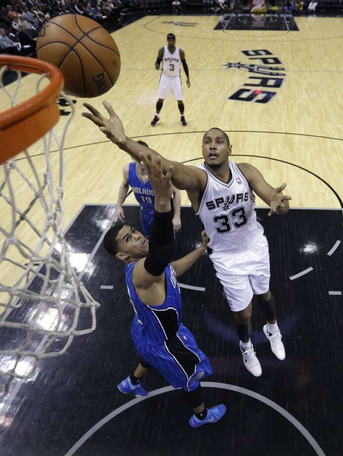 The Spurs' Boris Diaw (33) shoots over Orlando Magic's Tobias Harris (left) on April 3, 2013, at the AT&T Center. San Antonio won 98-84.)