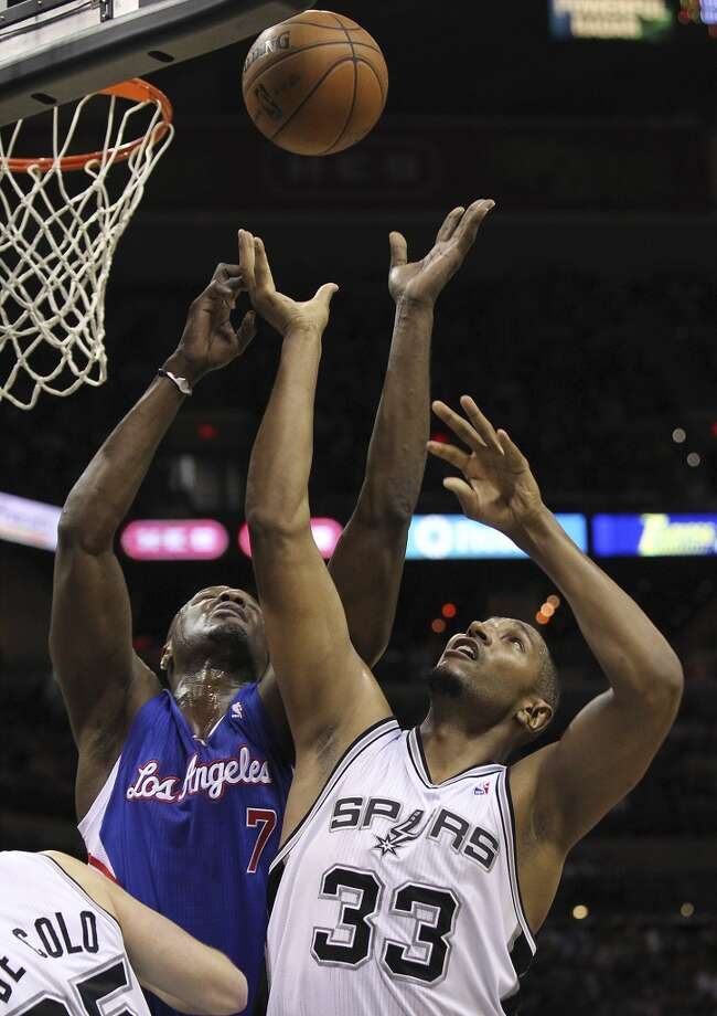 The Spurs' Boris Diaw (33) and Clippers' Lamar Odom (7) go up for rebound at the AT&T Center on March 29, 2013. The Spurs defeated the Clippers, 104-102.
