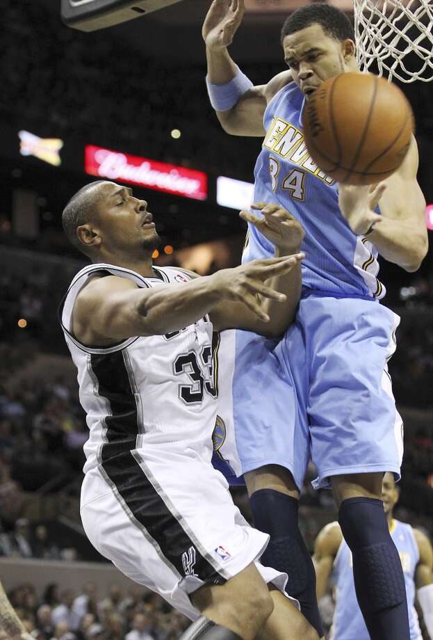 The Spurs' Boris Diaw (33) passes out of trouble against the Denver Nuggets' JaVale McGee (34) at the AT&T Center on March 27, 2013.