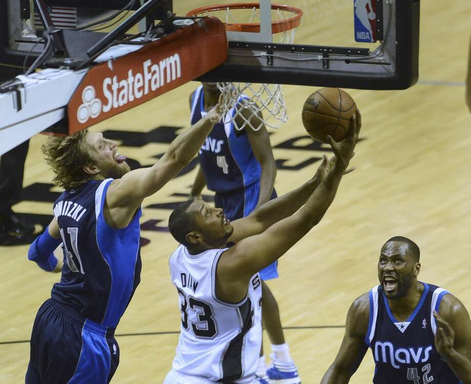Boris Diaw of the Spurs scores on a reverse as Dirk Nowitzki (left) and Elton Brand (42) of the Dallas Mavericks defend on at the AT&T Center on March 14, 2013.