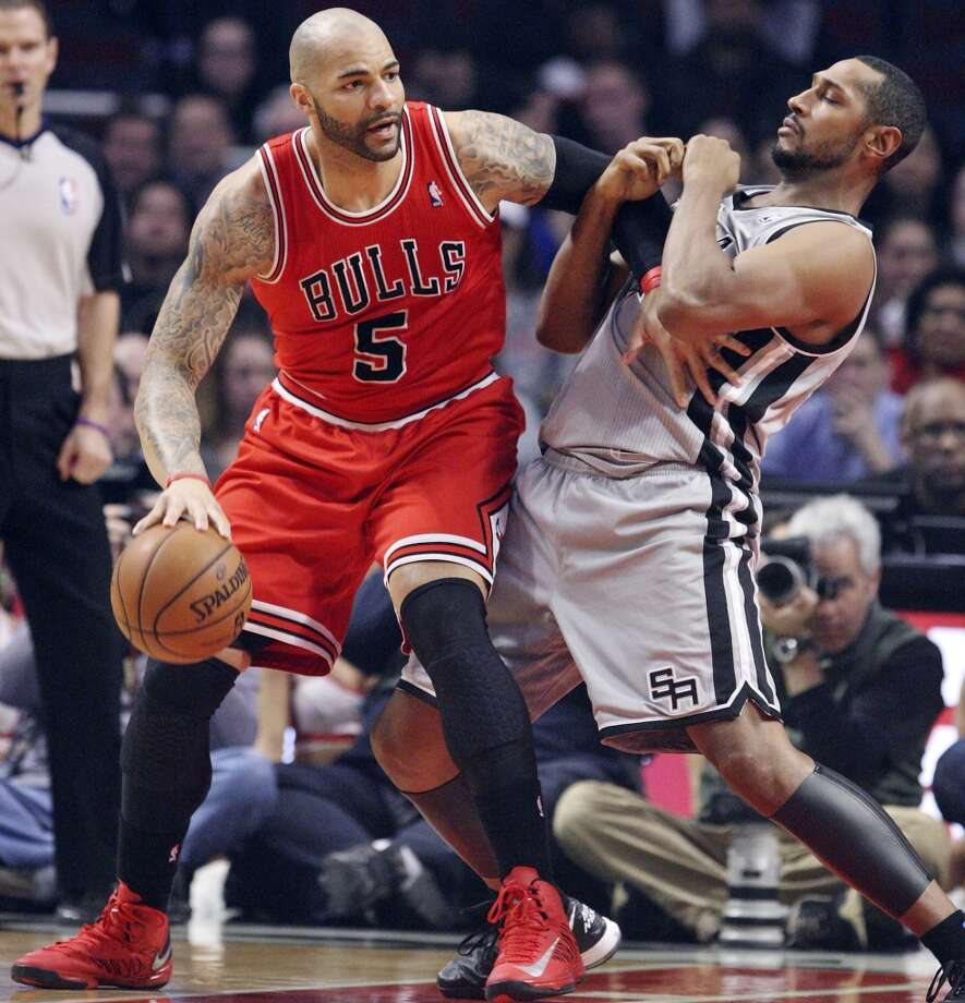 The Spurs' Boris Diaw defends Chicago Bulls' Carlos Boozer on Feb. 11, 2013  in Chicago.