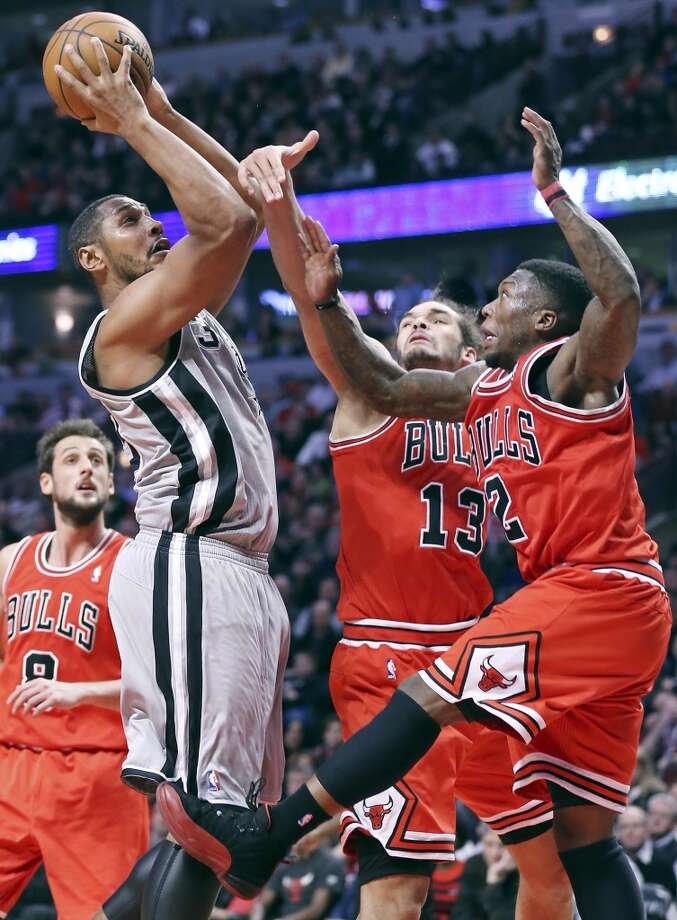 The Spurs' Boris Diaw drives to the basket against Chicago Bulls' Joakim Noah (center left) and Nate Robinson on Feb. 11, 2013 in Chicago. The Spurs won 103-89.