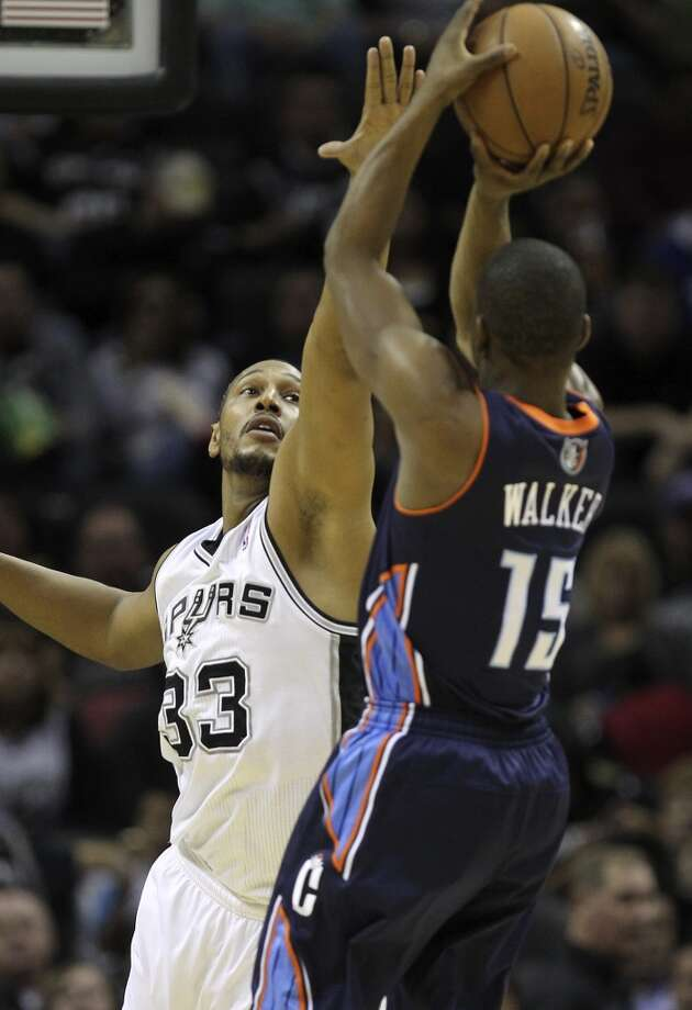 The Spurs' Boris Diaw reaches in to try and block a shot by Charlotte Bobcats' Kemba Walker at the AT&T Center on Jan. 30, 2013. The Spurs won 102-78.