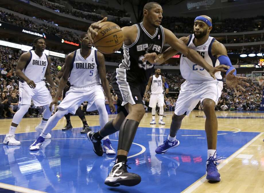 The Spurs' Boris Diaw (33) attempts to get through the defense of Dallas Mavericks' Jae Crowder (9), Bernard James (5) and Vince Carter (25)  on Jan. 25, 2013, in Dallas. The Spurs won 113-107.