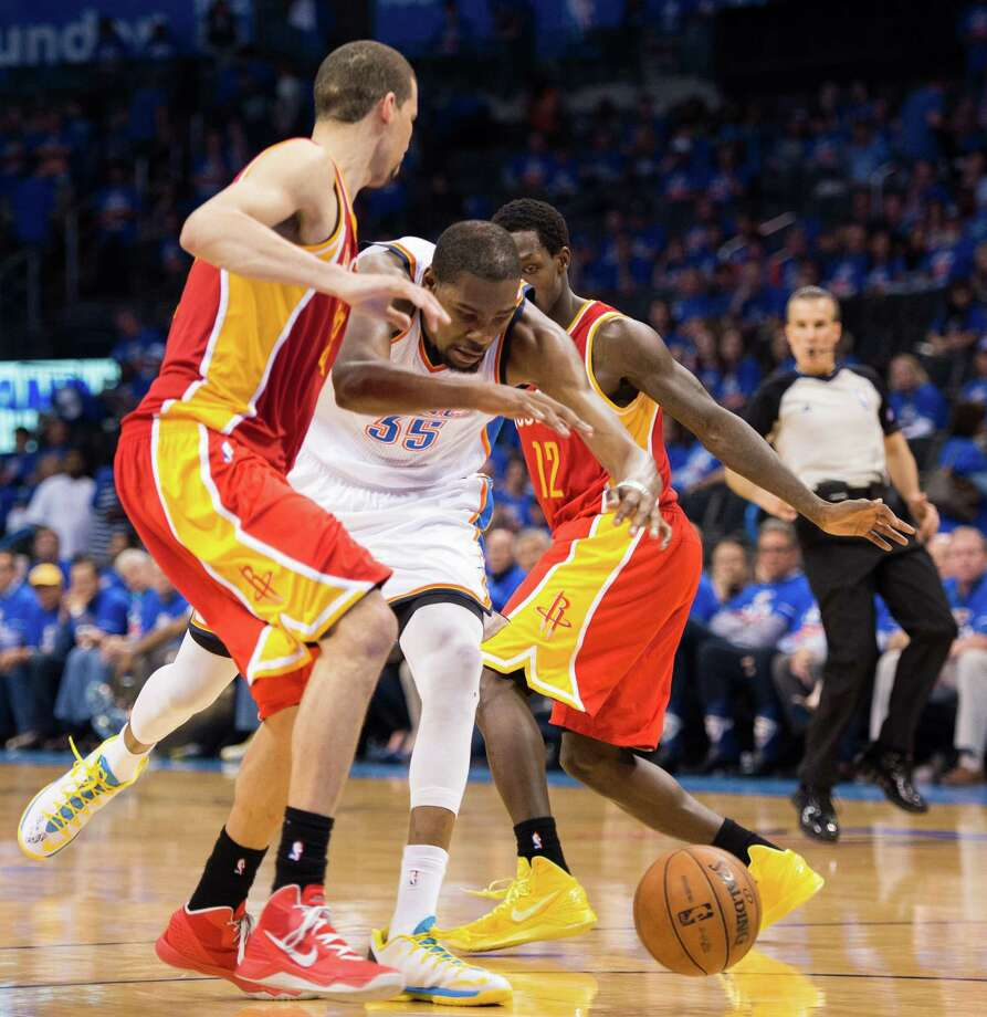 The Rockets' plan to run as many defenders as possible at Kevin Durant - in this case Francisco Garcia, left, and Patrick Beverley - isn't keeping the Thunder star from scoring but has helped produce wins in the last two games. Photo: Smiley N. Pool, Staff / © 2013  Houston Chronicle