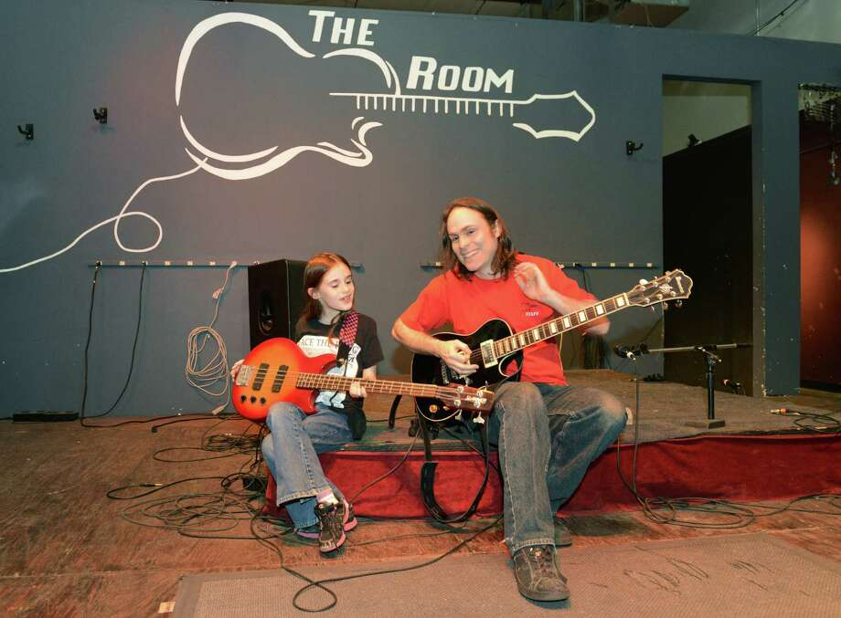 "Owner Vern Nickerson plays guitar with his daughter, Lily Nickerson, 9, on stage at The Room, a music venue that caters to kids, in Brookfield, Conn. on Saturday, April 20, 2013.  In May, The Room will be participating in ""Hate the Hate,"" an anti-bullying-themed music program. Photo: Tyler Sizemore / The News-Times"