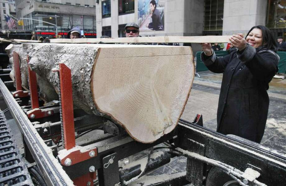 Iveth Bowie, of Stamford, Conn., helps carry a piece of lumber cut from the trunk of the annual Rockefeller Center Christmas tree, in New York,  Friday, Jan. 8, 2010, that will become part of her new Habitat for Humanity home in Connecticut. This is the third year the Rockefeller Center tree has been milled to serve as lumber for Habitat for Humanity. (AP Photo/Richard Drew) Photo: Richard Drew, AP Photo/Richard Drew