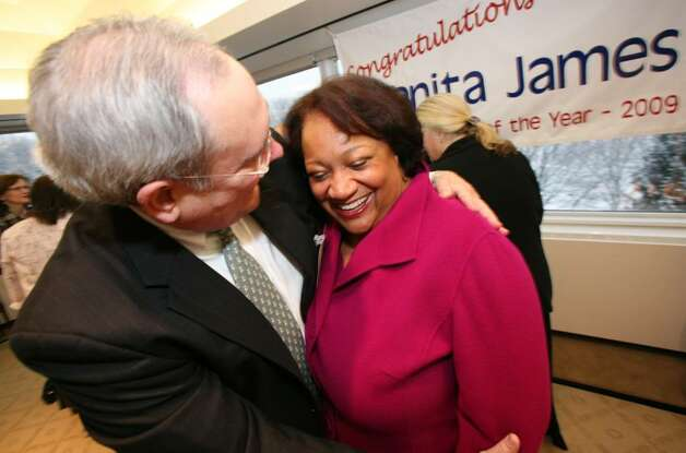 Stamford Citizen of the Year Juanita James is hugged by 2009 Citizen of the Year Richard Taber during Ms. James surprise party at the Pitney Bowes World Headquarters in Stamford Friday morning. Photo: David Ames, David Ames/For Stamford Advocate / Stamford Advocate
