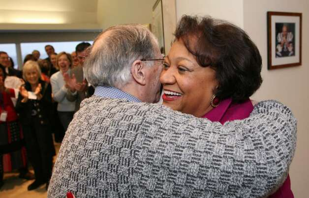 Stamford Citizen of the Year Juanita James is hugged by Kurt Zimbler Commander of the Jewish War Veterans of the USA who is the representative of the  sponsoring organization for the award during Friday mornings surprise announcement at the Pitney Bowes World Headquarters in Stamford. Photo: David Ames, David Ames/For Stamford Advocate / Stamford Advocate
