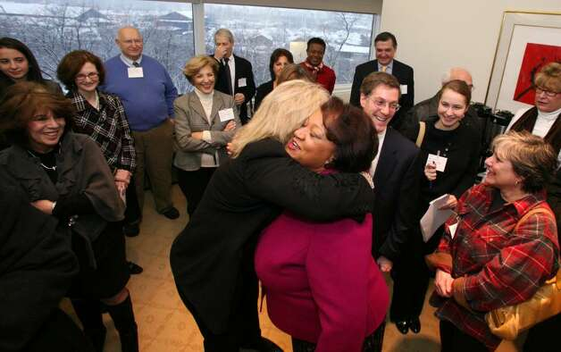 Stamford Citizen of the Year award recipient Juanita James is hugged by well wishers during her surprise party Friday morning at the Pitney Bowes World Headquarters where she is Chief of Marketing & Communications. Photo: David Ames, David Ames/For Stamford Advocate / Stamford Advocate