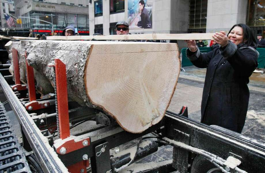 Iveth Bowie, of Greenwich, Conn., helps carry a piece of lumber cut from the trunk of the annual Rockefeller Center Christmas tree, in New York,  Friday, Jan. 8, 2010, that will become part of her new Habitat for Humanity home in Connecticut. This is the third year the Rockefeller Center tree has been milled to serve as lumber for Habitat for Humanity. (AP Photo/Richard Drew) Photo: Richard Drew, AP