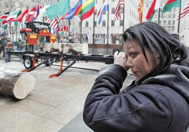 Iveth Bowie, of Stamford, Conn., wipes a tear as she watches a portion of the trunk of the annual Rockefeller Center Christmas tree cut into lumber, in New York,  Friday, Jan. 8, 2010, that will become part of her new Habitat for Humanity home in Connecticut. This is the third year the Rockefeller Center tree has been milled to serve as lumber for Habitat for Humanity. (AP Photo/Richard Drew) Photo: Richard Drew, AP Photo/Richard Drew