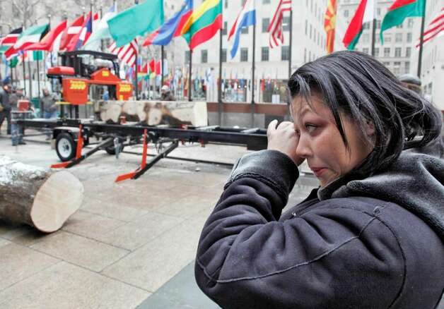 Iveth Bowie, of Greenwich, Conn., wipes a tear as she watches a portion of the trunk of the annual Rockefeller Center Christmas tree cut into lumber, in New York,  Friday, Jan. 8, 2010, that will become part of her new Habitat for Humanity home in Connecticut. This is the third year the Rockefeller Center tree has been milled to serve as lumber for Habitat for Humanity. (AP Photo/Richard Drew) Photo: Richard Drew, AP
