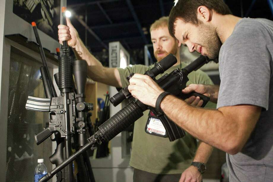 Jayden Quinlan (left) and Riley McElroy look at firearms  as exhibitors begin setting up for the NRA's annual meeting in Houston. Photo: Johnny Hanson / Houston Chronicle